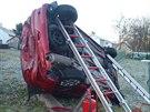 Hasiči vůz podepřeli, aby se neskutálel ze svahu. (17. prosince 2013)