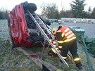 Hasiči vůz podepřeli žebříky, aby se neskutálel ze svahu. (17. prosince 2013)