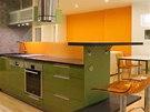 Zelená a oranžová barva se v kuchyni opakují.