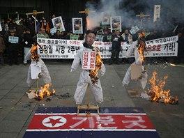 V jihokorejském Soulu lidé naopak protestovali. Na snímku hoří podobizny tří...