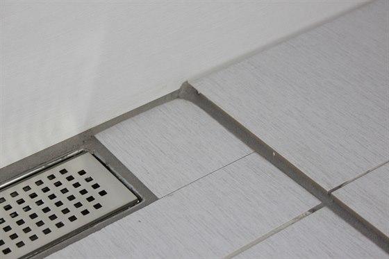 Takto vypadají detaily pokládky rektifikované dlažby ve sprchovém koutě....