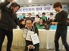 Student v masce Kim Čong-una dává palec dolů studentovi s maskou vůdcova strýce...