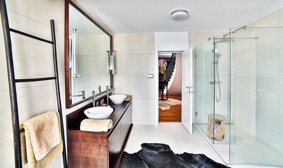 Koupelna má bezbariérový sprchový kout, zařízený teakovým špalkem, na který se