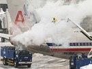 Pracovníci letiště v Bostonu rozmrazují letadlo během sněhové bouře, která
