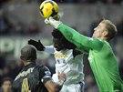 Wilfried Bony (v bílém) ze Swansea v souboji s brankářem Joem Hartem z...