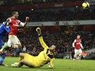 Theo Walcott (v červeném) z Arsenalu překonává gólmana Davida Marshalla z...