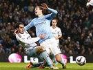 Edin Džeko z Manchesteru City padá po souboji s Joeym O'Brienem z West Hamu.
