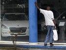 Kubánec si prohlíží ceny Peugeotů. Na Kubě si už nové auto může oficiálně...