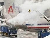 Pracovníci letiště v Bostonu rozmrazují letadlo během sněhové bouře, která...