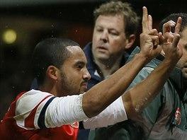 POSMĚŠNÉ GESTO. Theo Walcott, byť na nosítkách v nefotbalové pozici, ukazuje...