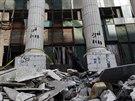 Policajt stojí před zničenou budovou soudu po explozi v Imbabě, severní části...