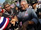 Bývalý vicepremiér Suthep Thaugsuban (v proužkované košili) se zdraví s...