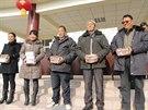 Vesničané spokojené ukazují bankovky, které dostali za podíl v prosperujícím...