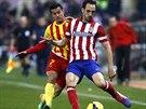 PŘETLAČOVANÁ. O míč bojuje Francisco Juanfran z Atlética Madrid (vpravo) s...