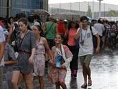 RYCHLE PRYČ. Diváci v Melbourne Parku se běží schovat před deštěm.