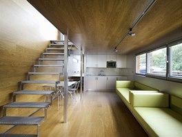 Společný obývací prostor je vybaven nábytkem vyrobeným na míru a obložený