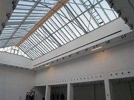 Centrální prostor výstavní síně prochází až do druhého patra a je osvětlen...