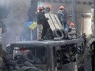 My se nedáme! Demonstranti vyzbrojení dělnickými helmami vartují na ohořelém...