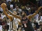 LeBron James (vpravo) z Miami fauluje Tima Duncana ze San Antonia.