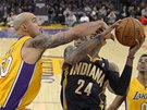 Paul George z Indiany se snaží udržet míč, napadá ho  Robert Sacre z LA Lakers.