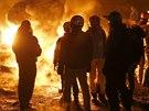 Demonstranté se ohřívají u jedné z barikád v centru Kyjeva. (24. ledna 2014)