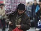 Muž s těžkým nákladem na rameni si kontroluje jízdenku na vlak před Hlavním...