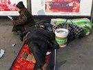 Před pekingským nádražím lidé odpočívají a čekají, až jim pojede vlak. Ten je v...
