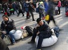 Před nádražím v Pekingu lidé čekají na svůj vlak. Na oslavy Nového roku míří za...