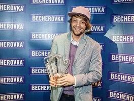 Adam Tureček při přebírání ceny a poháru, jehož autorem je Marcel Mochal.