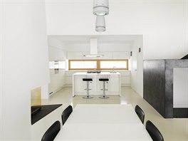 Židle jsou černé, kuchyňská linka a stůl bílé. V této domácnosti panuje pevný...