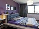 Ložnice rodičů je laděna do odstínů fialové. Vybavení respektuje přírodní ráz