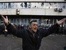 Muž v bosenské Tuzle se obrací k demonstrantům, aby přestali házet kameny na...
