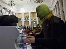 Maskovaný pianista hraje na kyjevské radnici (Ukrajina, 1. únor 2014).