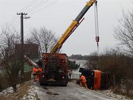 Při údržbě silnice sjel posypový vůz na ledovce ze silnice a převrátil se na