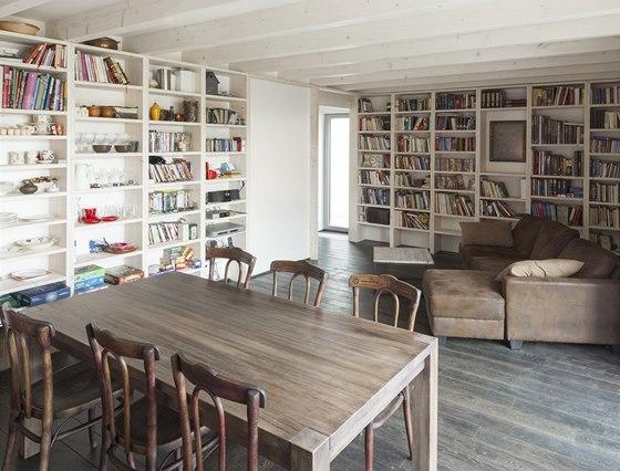 Obytný prostor v přízemí lemují vysoké bílé police knihoven podél stěn.