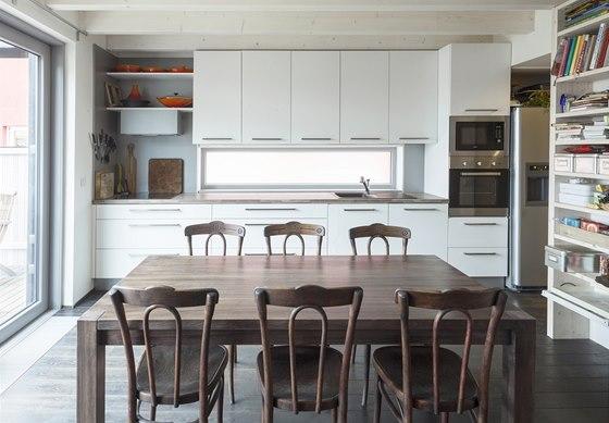 Bílou kuchyňskou linku doplnil velký stůl z masivu.