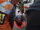 Záchranáři odnášejí tělo muže usmrceného při útoku na péšávárské kino (11.
