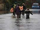 Pracovník obchodu pomáhá rodině odnést nákum přes zaplavené město (Staines nad