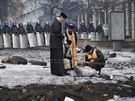 Pravoslavní kněží zapalují svíčky před kordonem policistů v centru hlavního...