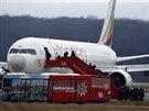 Cestující s rukama za hlavou za dohledu policie opouštějí letadlo, které unesl...