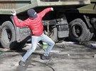 Jeden z opozičních demonstrantů hází dlažební kostku směrem k policistům. (18....