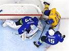 Švédský hokejista Daniel Sedin se snaží dorazit puk za záda slovinského gólmana