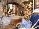 Dominantou sv�tnice je otev�en� zaklenut� ohni�t�, poz�statek �ern� kuchyn�.