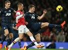 Kieran Gibbs z Arsenalu (uprostřed) svádí souboj o balón s Michaelem Carrickem...