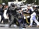 Zdravotníci odnášejí zraněného policistu, zatímco jeho kolegové kontrolují...
