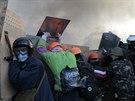 Demonstranti se při střetech s policí snaží chránit štíty (Kyjev, 19. února...