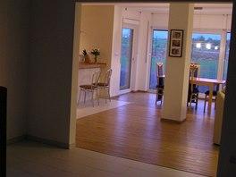 Ze vstupní haly pronikal do obývacího pokoje zbytečně studený vzduch.