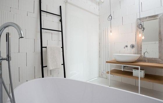 Dětská koupelna je celá bílá. Nechybí v ní vana a jednoduchý žebřík na ručníky.