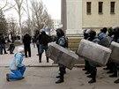 Doněck. Mladá Ukrajinka klečí před příslušníky speciální zásahové jednotky...