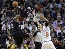 LeBron James z Miami při střelbě. Blokovat se pokouší Pablo Prigioni z týmu New